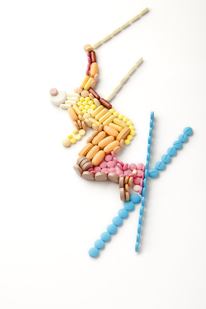 Doping pills and drugs in the shape of a winter jumping skier. photo