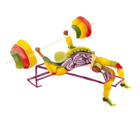 Fruits and vegs in the shape of a healthy muscular bodybuilder lifting a barbell. 免版税图像