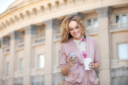 A beautiful woman checking email on the mobile phone and holding a cup of take away coffee