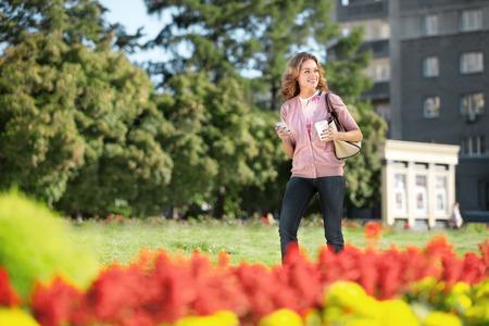 Eine schöne Frau mit einem Mobiltelefon und Kaffee zu Fuß zu gehen in einem Stadtpark