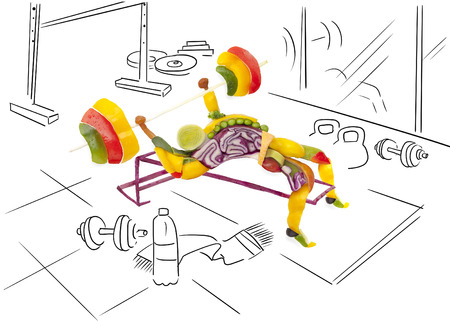 Fruits and vegs in the shape of a healthy muscular bodybuilder lifting a barbell at the gym. 免版税图像