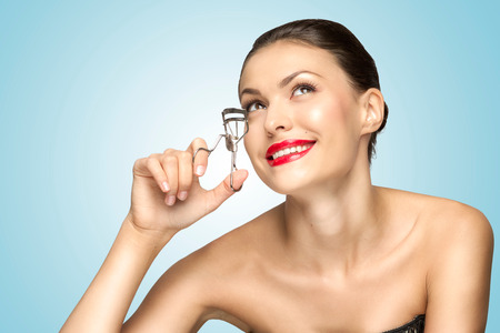 curler: A beautiful fashion girl holding an eyelash curler in her hand as a makeup accessory.