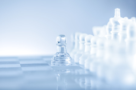 Single pawn staying against a full set of chess pieces.