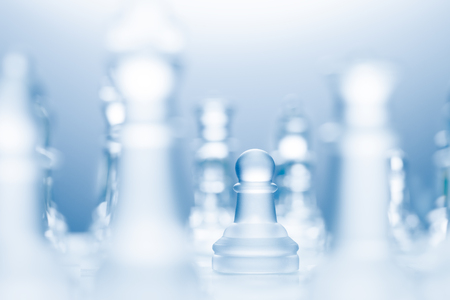 A conceptual photo of a transparent pawn made of glass on a chessboard. photo