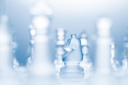pensamiento estrategico: Una foto conceptual de un caballero transparente sobre un tablero de ajedrez hacer un movimiento en forma de l. Foto de archivo