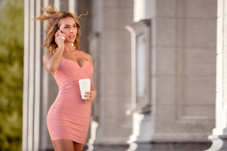 A pretty woman in a pink dress talking via mobile phone and holding a coffee cup. photo