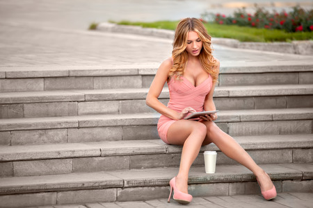 A businesswoman with a tablet and coffee cup sitting on stairs. photo