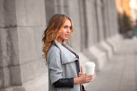 A pretty woman with a coffee to go against urban scene. photo
