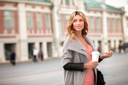 to go cup: A pretty woman holding a coffee to go cup against urban scene. Stock Photo