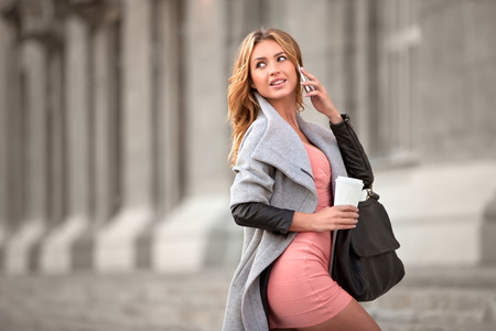 handbag: A businesswoman talking via mobile phone and holding a coffee cup against urban scene. Stock Photo
