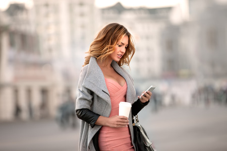 A businesswoman checking email via mobile phone and holding a coffee cup against urban scene.