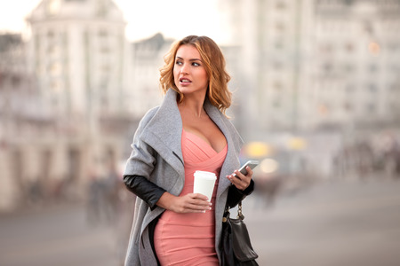 A businesswoman with a mobile phone holding a coffee cup against urban scene.