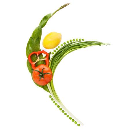 Vegetables and fruits arranged in a shape of a happy slim ballet dancer. 免版税图像