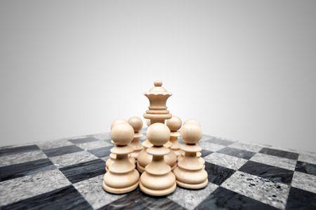 fearless: Fearless pawns standing in allround defence ready to fight for a chess queen. Stock Photo