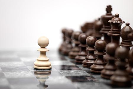 Een pion blijven tegen volledige set van schaakstukken. Stockfoto