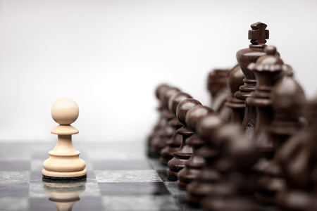 chess board: One pawn staying against full set of chess pieces.
