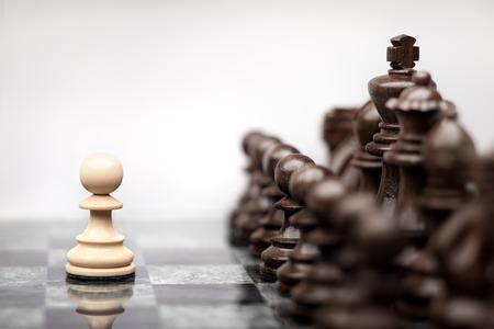 Un pion restant contre le jeu complet de pièces d'échecs. Banque d'images - 26865338