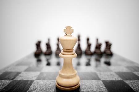 La foto significativa de rey del ajedrez permanecer ante el conjunto de otras piezas de color. Foto de archivo - 26865344