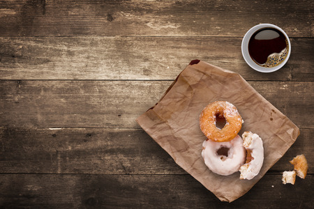 donut: A morning lunch in the office consisted of a cup of black takeaway coffee and tasty donuts.
