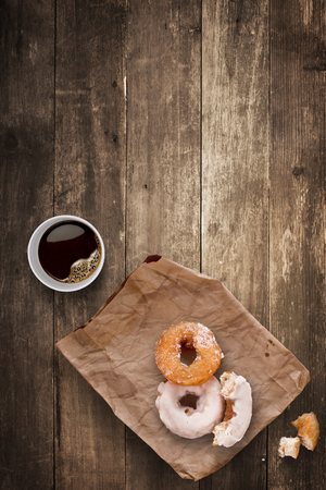 A morning lunch in the office consisted of a cup of black takeaway coffee and tasty donuts. photo