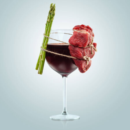 Interesting composition of meat and plants wiredly connected over the wine glass. 免版税图像