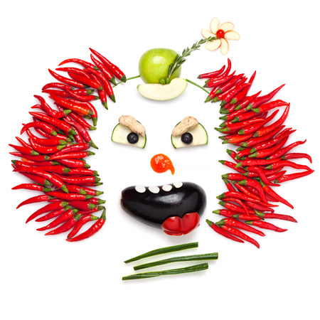 A creative food concept demonstrating a creepy halloween clown with the help of chilli pepper and other vegetables. photo