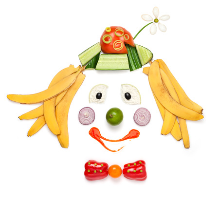 A creative food concept demonstrating a portrait of smiling clown made of vegetables and fruits in a menu for children. photo