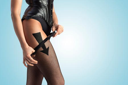 A beautiful sexy girl taking off her fishnet pantyhose according to the arrow sign. photo