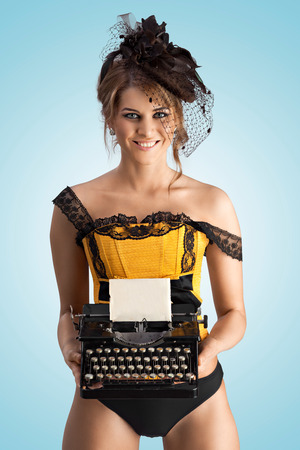 lustful: A photo of cheerful pin-up girl in vintage corset holding typewriter.