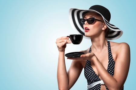 comida rica: Una foto de la vendimia creativa de una hermosa chica pin-up beber té y mostrando buenos modales en la mesa.