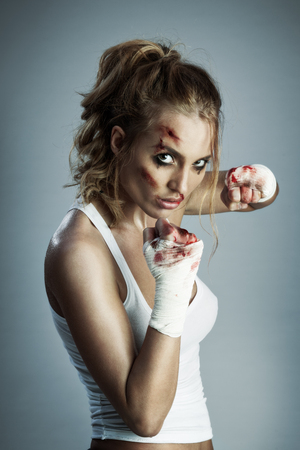 blood sport: A photo of woman standing in fight position with blood over the face and fists.