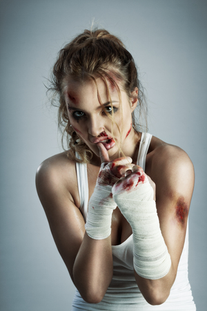 practicing: A photo of woman standing in fight position with blood over the face and fists.