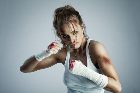 punched: A photo of woman standing in fight position with blood over the face and fists.