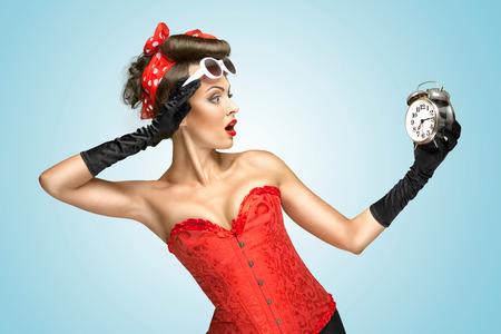 vestidos de epoca: La foto conceptual de una chica pin-up en ropa interior glamour y guantes miran el reloj Foto de archivo
