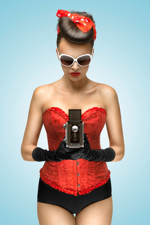 sexy pictures: A photo of the pin-up girl in corset holding vintage camera