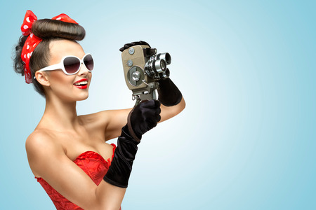 A photo of the pin-up girl in corset and gloves holding vintage 8mm camera  Stock Photo