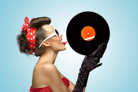 A photo of glamorous pin-up girl touching vinyl LP with tongue