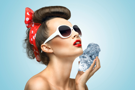 A hot photo of beauty touching her face with the piece of ice holding in her hands  photo
