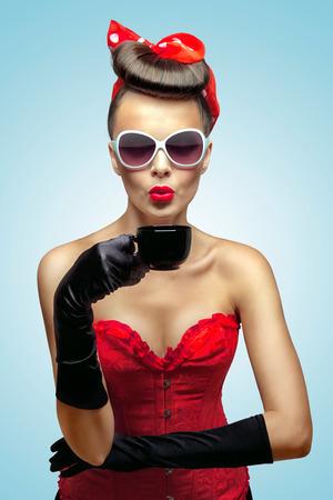De vintage foto van glamour pin-up girl dragen vintage handschoenen en koelen van een warme kop koffie Stockfoto