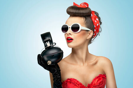 pin up vintage: Una foto bella di bella ragazza detiene cuffie in mano