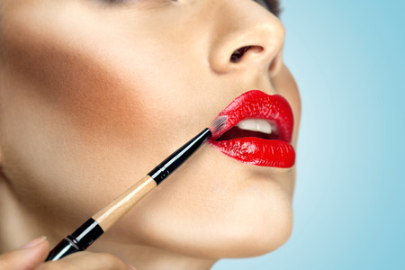 Fashion photo of face makeup demonstrating lips of a cute girl painted with bright lipstick with the hepl of brush  photo