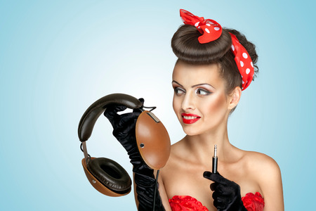 The retro photo of a cute pin-up girl that holds vintage headphones and wants to listen to the music  photo