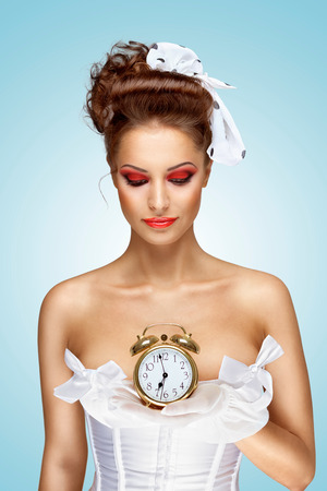 sexy bride: A beautiful vintage pin-up girl in a white wedding dress being late in the morning and holding a retro alarm clock in her hand.