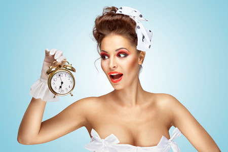 impatient: A beautiful vintage pin-up girl in a white wedding dress being late in the morning and holding a retro alarm clock in her hand.