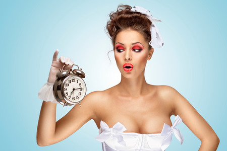 A beautiful vintage pin-up girl in a white wedding dress being late in the morning and holding a retro alarm clock in her hand.