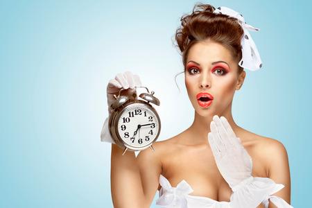 vestidos de epoca: Una niña hermosa de la vendimia de pin-up en un vestido de novia blanco de llegar tarde por la mañana y que sostiene un reloj de alarma retro en la mano.