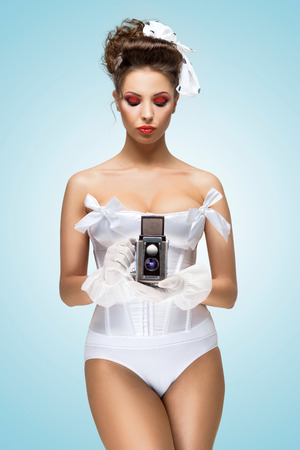 pinup girl: A photo of the pin-up girl in corset holding vintage camera. Stock Photo