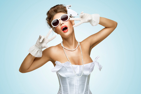 The retro photo of a glamorous bride with stylish makeup in a vintage corset showing V sign. photo