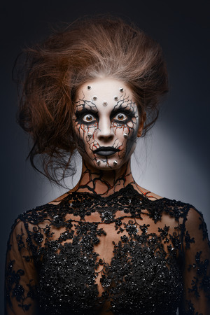 A girl standing like a statue in a creepy halloween costume of a witch with peircing and cracked face paint. photo