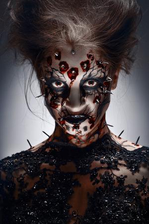 ひびの入ったフェイス ペイントと流血 peircing 魔女の不気味なハロウィーン化粧。 写真素材